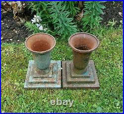 Small pair antique cast iron goblet-shaped urn planters on stepped plinths